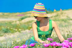 Attractive girl on a field with colorful flowers. And the blue sky Royalty Free Stock Photos