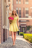 Attractive girl with flowers. Full length portrait of attractive girl in dress holding flowers, looking away and smiling while walking outdoors Stock Image