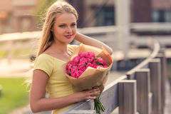 Attractive girl with flowers. Portrait of attractive girl in dress holding flowers, looking away and smiling while standing outdoors Stock Photo