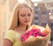 Attractive girl with flowers. Portrait of attractive girl in dress holding flowers, looking at them and smiling while standing outdoors Royalty Free Stock Photography