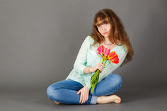 Attractive girl. With flowers sitting on gray background Royalty Free Stock Photography