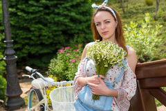 Attractive girl with flowers standing near bike. Attractive girl with large bouquet of little white flowers while leaning on railing of a bridge outside Stock Photography