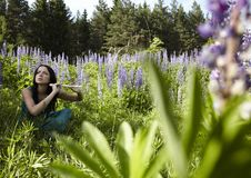 Attractive girl with flute sitting in summer field Stock Images