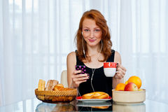 Attractive girl with freckles eating breakfast Royalty Free Stock Photography