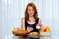 Attractive girl with freckles eating breakfast Stock Photography