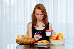 Attractive girl with freckles eating breakfast Stock Images