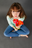 Attractive girl. Funny portrait of attractive girl with flowers sitting on gray background. Distorted perspective Royalty Free Stock Photos