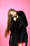 Attractive girl in fur coat in studio Stock Photography