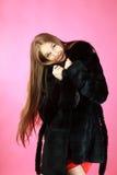 Attractive girl in fur coat in studio Stock Photography
