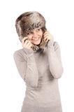 Attractive girl in a fur hat isolated on white. Over white background stock photography