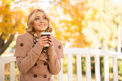 Attractive girl getting refreshment with coffee. Sitting on the bench in the park in autumn Royalty Free Stock Photos