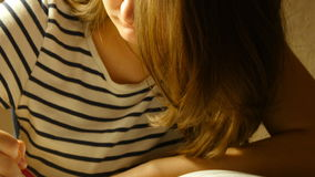 Attractive girl in glasses draws coloring book. Close up stock footage