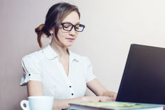 Attractive girl with the glasses typing on a laptop. Working in office. business woman lady stock image