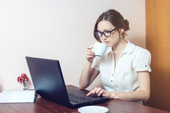 Attractive girl with the glasses typing on a laptop. Working in office. business woman lady stock photo