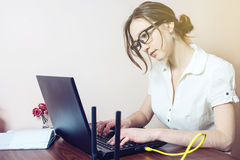 Attractive girl with the glasses typing on a laptop. Working in office. business woman lady stock photos