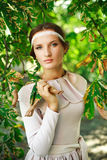 Attractive girl in green-brown foliage Royalty Free Stock Image