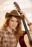 Attractive girl with guitar. Attractive girl leaning on guitar, dressed in country style Stock Image