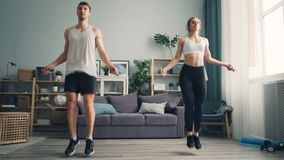 Attractive girl and guy jumping rope in studio apartment focused on exercise stock video footage