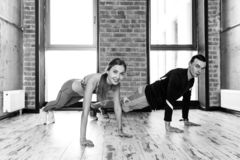 Attractive girl and guy performing press up in the room stock photo