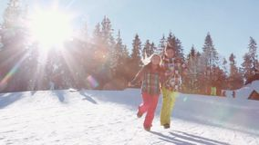 Attractive girl and handsome brunette guy in winter sports wear. Young lovely couple are holding their hands and running. Attractive blonde girl and handsome stock video footage