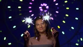 An attractive girl is happy with a holiday with fireworks in her hands. slow motion. HD. An attractive happy girl is happy with a holiday with fireworks in her stock video footage