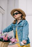 Attractive girl in hat sunglasses and denim jacket riding bicycle. On street stock photos