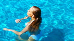 Attractive girl havin fun in swimming pool Stock Photos