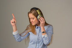 Attractive girl with headphones on gray background Stock Image