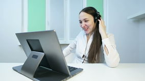Attractive girl in headphones speaks on the video camera on the laptop. stock video footage