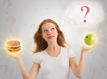 Attractive girl, healthy and unhealthy food Royalty Free Stock Photos
