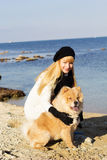 Attractive girl with her dog wearing warm clothes Royalty Free Stock Images