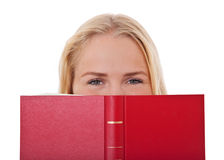 Attractive girl hides her face behind book Stock Images