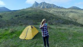 Attractive girl hiking makes selfie on smartphone on a background of mountains. A girl stands near the tent, camping