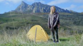 Attractive girl hiking stands at the entrance to the tent against the backdrop of the mountains. Enjoys the vacation