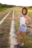 Attractive girl hitchhiking Royalty Free Stock Image