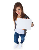 Attractive girl holding blank sign. High angle view of an attractive teenage girl holding blank sign. All on white background Royalty Free Stock Photo
