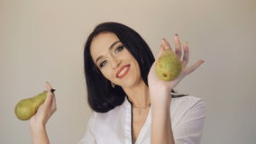 Attractive girl holding a juicy green pears in hands and smiling to camera 4K stock video