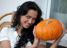 Attractive girl holding pumpkins and smiling Stock Photos