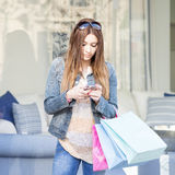 Attractive girl holding shopping bags and looking of phone. Stock Photo