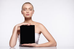 Attractive girl is holding tablet screen in the camera. An attractive girl is holding a tablet screen in the camera. Natural perfect skin. Beauty shot Stock Photos