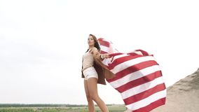 Attractive girl holding a waving American flag in nature. Independence Day, lifestyle, travel concept.  stock video footage