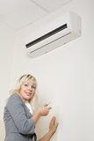 Attractive girl includes air conditioner Royalty Free Stock Image