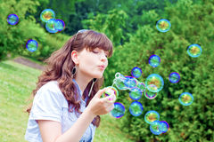 Attractive girl inflating colorful soap bubbles Royalty Free Stock Photo