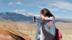Attractive girl in a jeans jacket takes photos of mountains on the phone 20s 4k. Attractive sporty 20s woman in a denim jacket and scarf takes pictures of stock footage