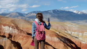 Attractive girl in a jeans jacket takes photos of mountains on the phone 20s 4k. Attractive sporty 20s woman in a denim jacket and scarf takes pictures of stock video footage