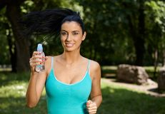 Attractive girl jogging in nature smiling Stock Photos
