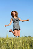 Attractive girl jumping in field Royalty Free Stock Images