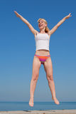 Attractive girl is jumping smiling. Vigorous blond woman in bikini and white shirt is jumping outdoors Stock Photo