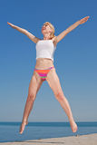 Attractive girl is jumping smiling. Vigorous blond woman in bikini and white shirt is jumping outdoors Royalty Free Stock Images