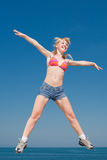 Attractive girl is jumping smiling. Vigorous blond woman in shorts and top of swimsuit is jumping outdoors Stock Photos